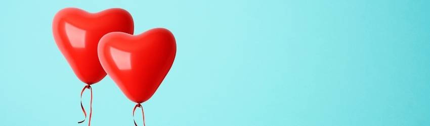 Two red heart balloons float next to each other on a teal background.