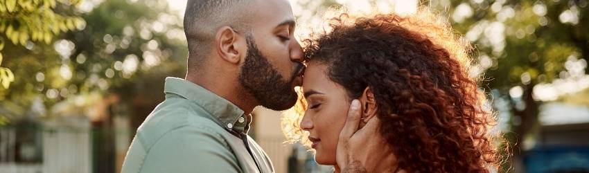 man kissing a woman on her forehead