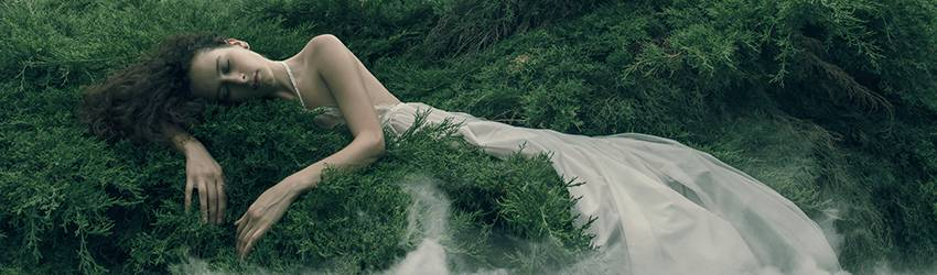 A woman with long brown hair and a white gown lays against the ground filled with lush, green trees. Her eyes are closed as if she is sleeping and she is embracing the tree.