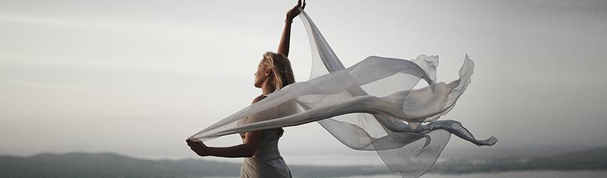 A blonde woman wearing a white gown holds up white gauzy fabric behind her, which appears to be blowing in the wind.